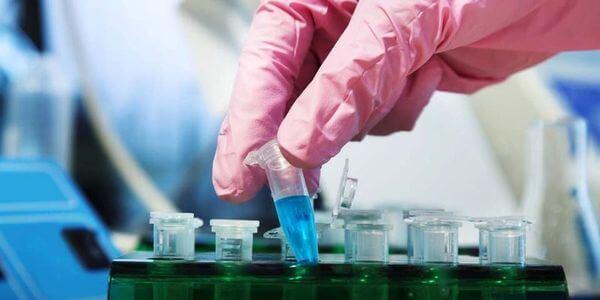 Биолог в перчатках и с колбой