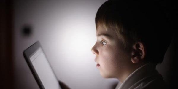 Ребенок смотрит на экран планшета