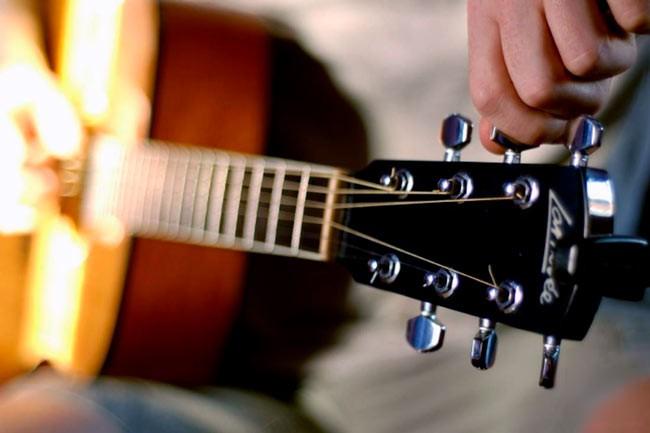 Настраивает гитару